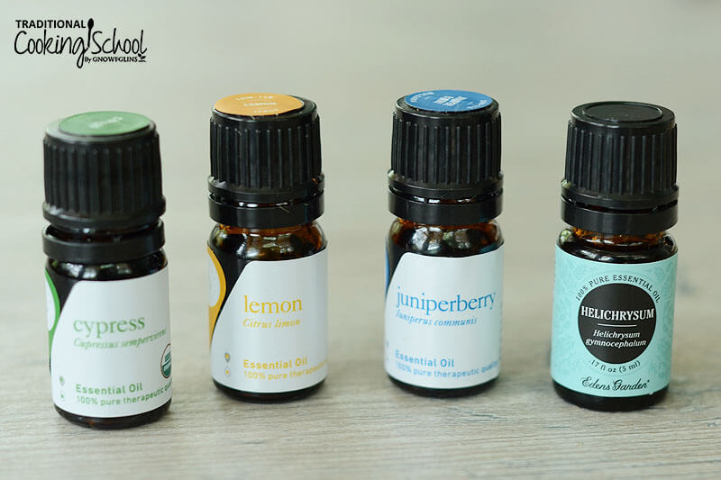 lineup of four essential oil bottles on a table, from left to right, cypress, lemon, juniper berry, and helichrysum