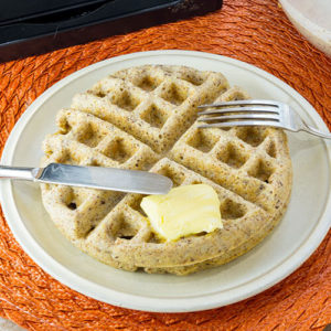 white plate on an orange place mat with one Belgian waffle, a slab of butter, and a knife and fork