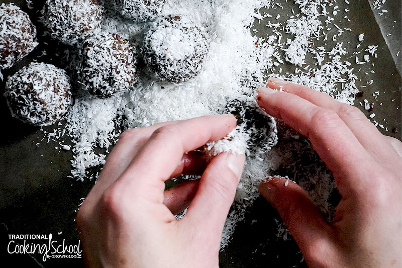 woman's hands coating cacao date balls with shredded coconut on a baking sheet
