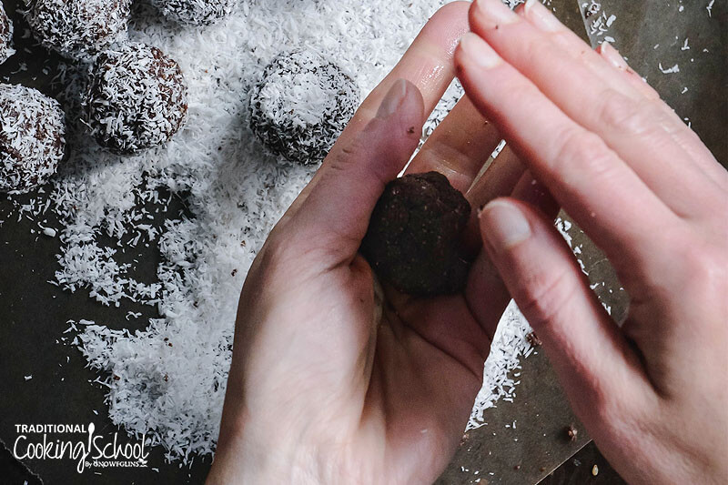 woman's hands shaping and rolling a cacao date bliss ball into a round shape