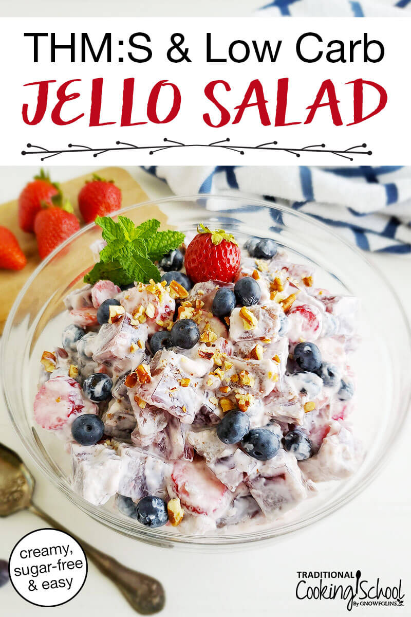 """photo of healthy jello salad in a clear glass bowl, garnished with a fresh strawberry and mint, next to a cuttingboard, spoon, and white and blue striped towel on a white counter, with text overlay: """"THM:S & Low Carb Jello Salad (creamy, sugar-free & easy)"""""""