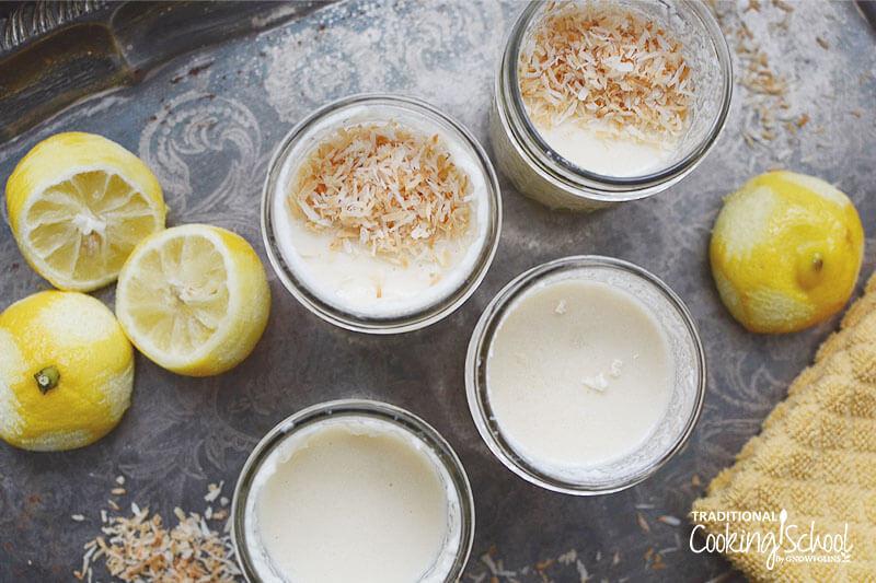 photo de pudding au citron dans une pinte -size pots Mason garnis de noix de coco râpée à côté de citrons qui ont été zestés