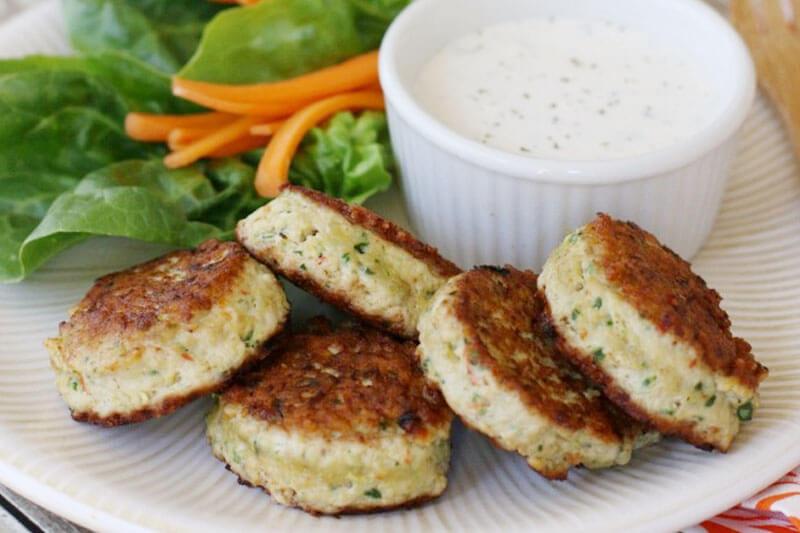 une assiette de poulet bouchées végétariennes à la peau dorée croustillante, disposées à côté de bâtonnets de carottes, de laitue et d'un petit bol de vinaigrette ranch à tremper dans