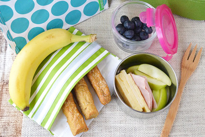photo of a quick and easy colorful lunch, including a banana, fresh blueberries, apple slices, sliced cheese, and more