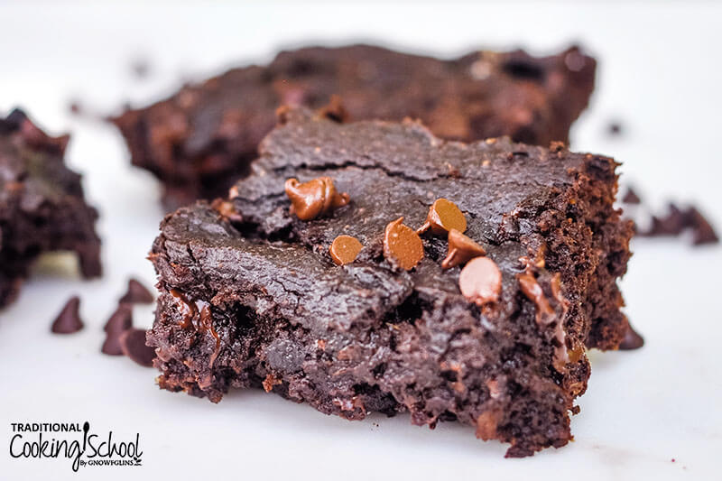 gooey gluten-free brownie on a plate with other brownies in the background, sprinkled with melty mini chocolate chips