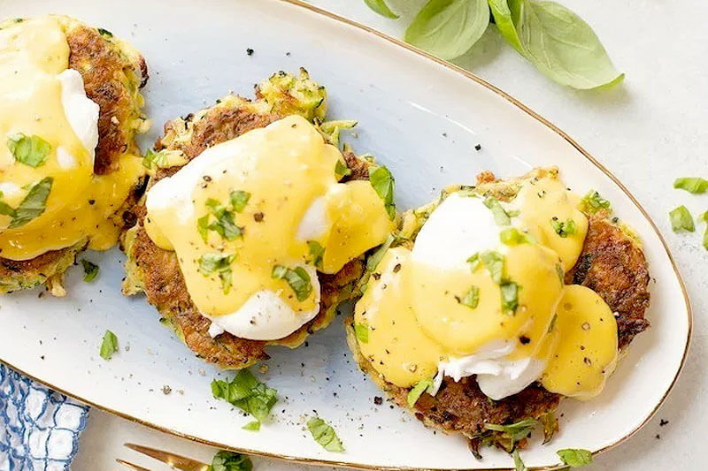 platter of three eggs benedict on crispy zucchini fritters, with fresh herbs for garnish