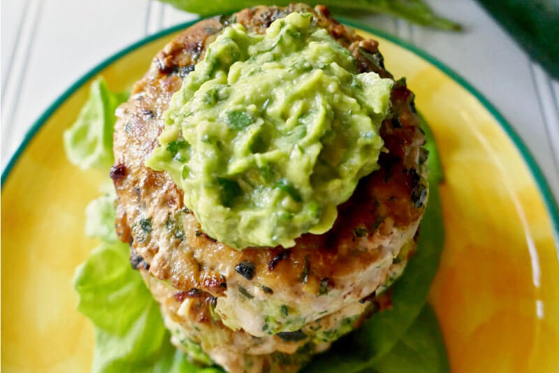 stack of small chicken zucchini burgers, topped with guacamole, on a bright yellow plate