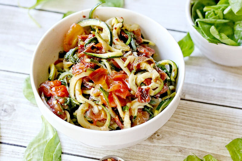 low carb pasta in a white bowl on a light wood background, with zucchini noodles, spinach, and tomatoes