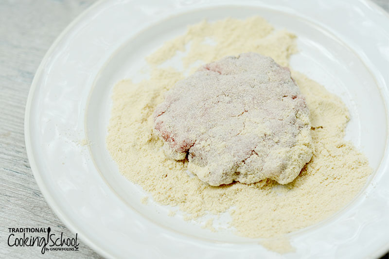 coconut flour on a plate with one raw sausage pattie being dredged and covered in the flour