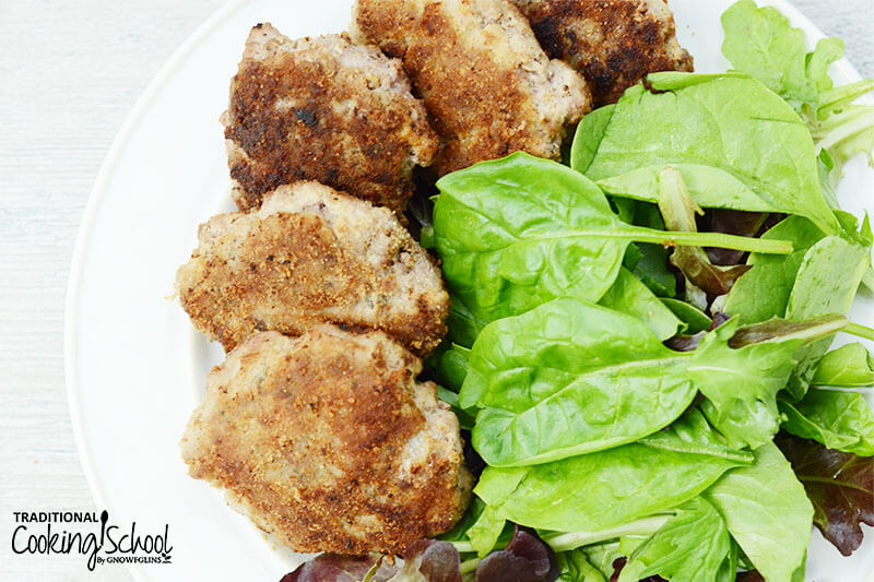crispy sausage patties arranged on a plate on a bed of fresh greens