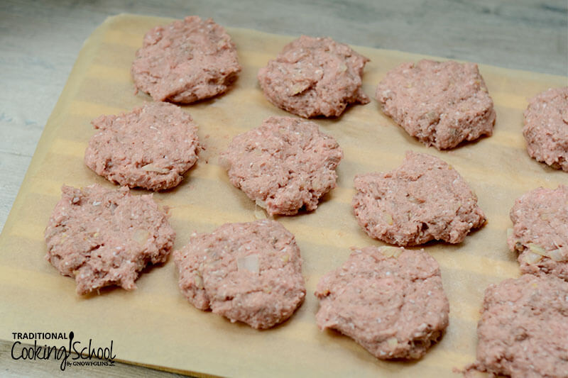 raw sausage patties arranged neatly on a sheet of parchment paper, ready to be cooked in a skillet