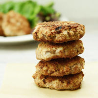 crispy sausage patties in a stack of three, with a plate of fresh greens in the background