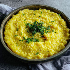 golden-colored creamy polenta in a wooden bowl on a rustic stone backdrop, and fresh green herbs for garnish