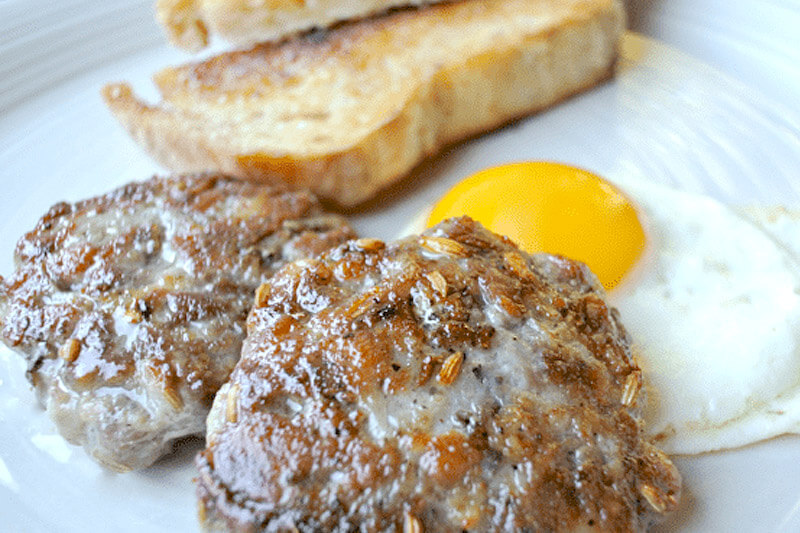 plate of pork sausage patties with an over easy egg and toast in the background