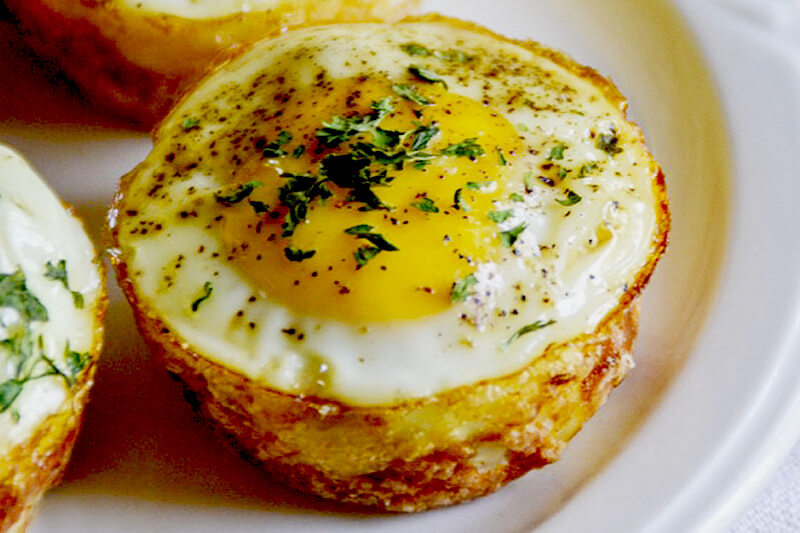 egg potato breakfast muffins that have been topped with fresh herbs and a sprinkle of black pepper