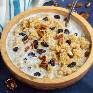 quinoa breakfast porridge, in a wooden bowl with milk and a spoon, topped with raisins and chopped pecans