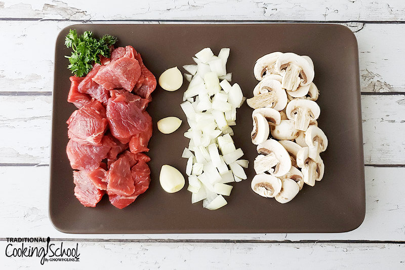 ingredients for making beef stroganoff, including sliced mushrooms, garlic cloves, diced onions, fresh parsley, and cubed stew meat