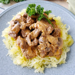 beef stroganoff on a bed of spaghetti squash, with a sprig of parsley for garnish