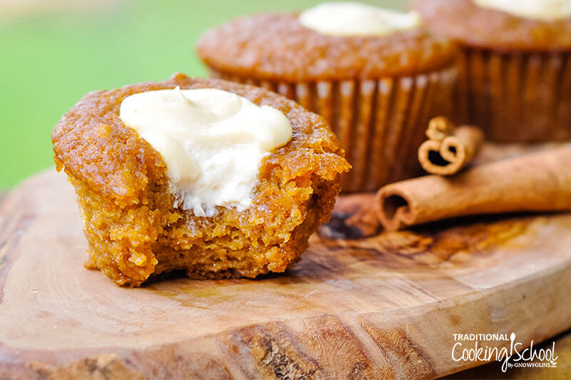 close-up shot of a pumpkin muffin with a bite taken out of it to reveal a pocket of cream cheese filling, with cinnaon sticks and other muffins in the background