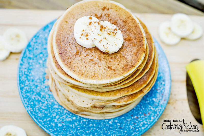 stack of fluffy gluten-free pancakes on a blue speckled plate, with two banana slices and a sprinkle of ground cinnamon for garnish