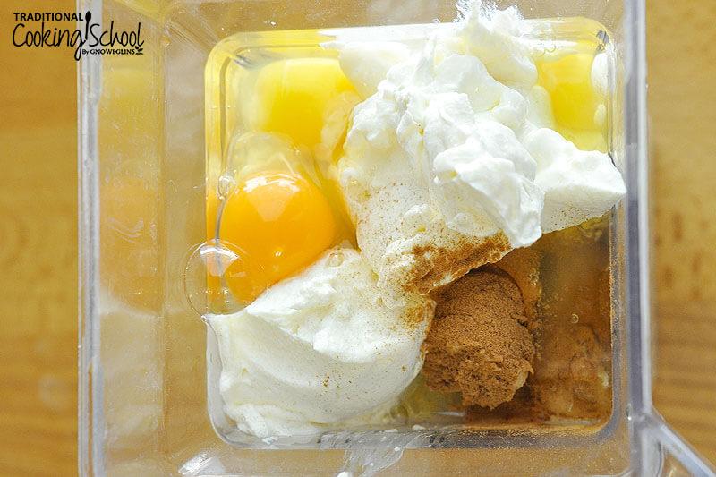 pancake ingredients in a blender, including bananas, eggs, yogurt, and cinnamon