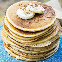 stack of fluffy, golden-brown pancakes on a blue speckled plate garnished with banana slices and a sprinkling of ground cinnamon
