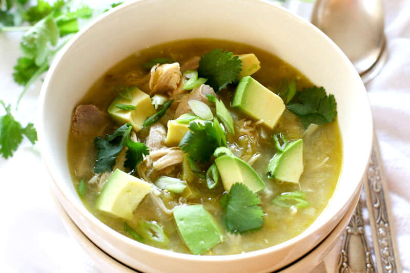 a crock pot chili recipe: white ceramic bowl of white chicken chili topped with fresh parsley and avocado chunks