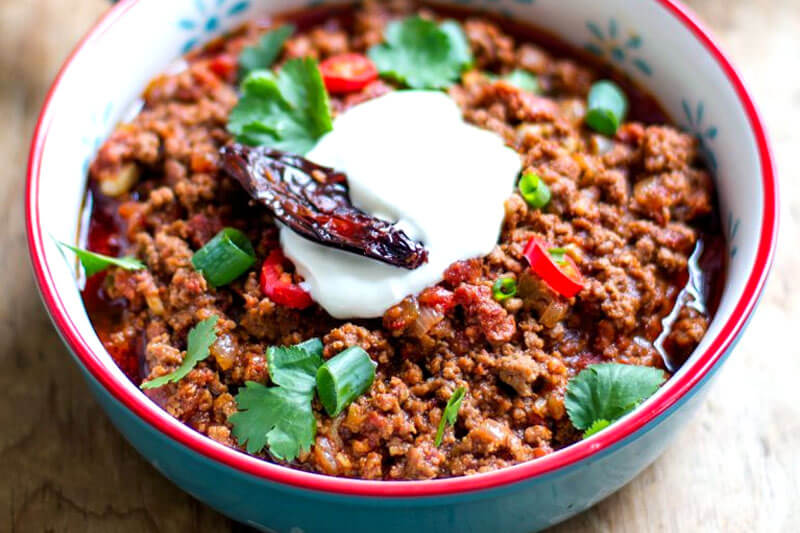 an Instant Pot chili recipe: chili con carne in a colorful ceramic bowl topped with fresh parsley, chives, sour cream, and sun dried tomato