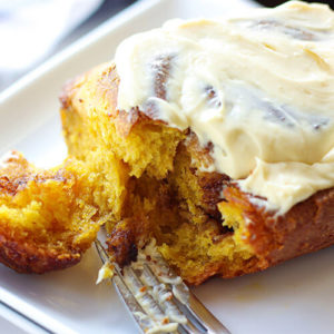 close-up shot of a sourdough pumpkin cinnamon roll slathered with cream cheese frosting, with a fork just having pulled a piece of the corner to reveal a moist, soft, tender texture inside
