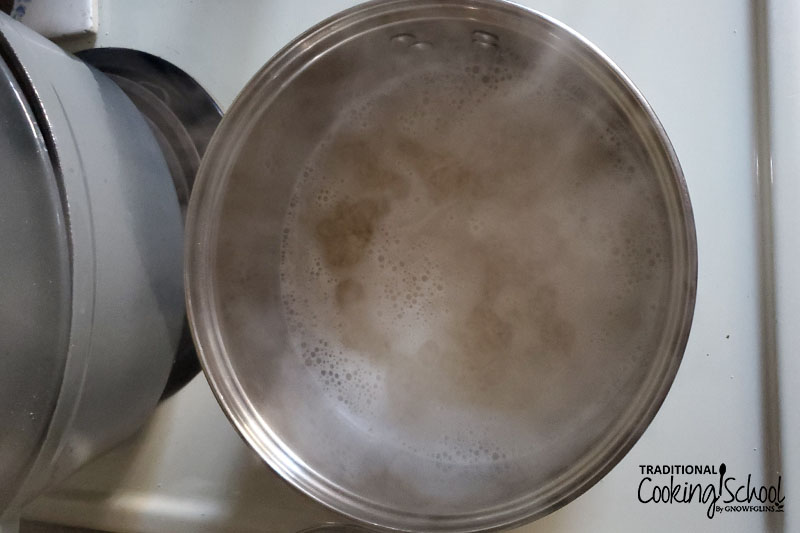 cooking rice on the stove in a stainless steel pot, with bubbles forming at the surface of the water and steam rising