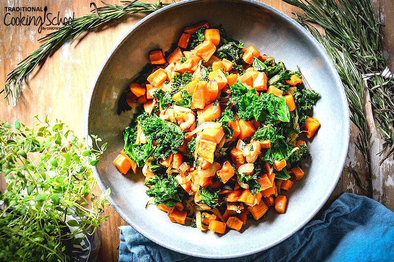 winter salad of warm kale and butternut squash and sweet potato chunks in a bowl, surrounded by a blue linen teacloth, fresh sprouts and rosemary