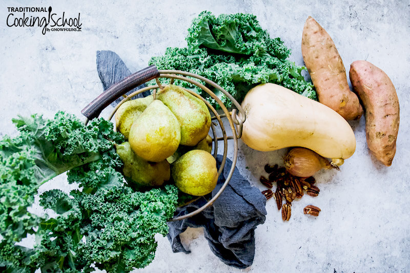 array of ingredients, including fresh kale, pears, butternut squash, pecans, and two sweet potatoes on a stoneware surface