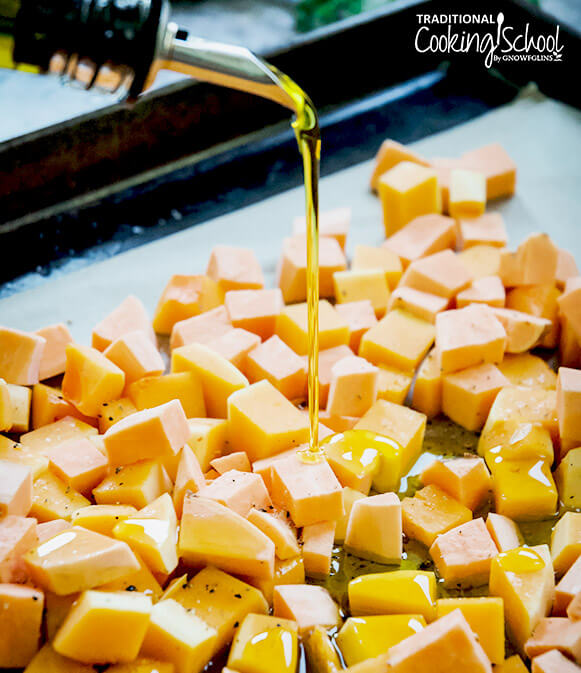 drizzling olive oil on a pan of butternut squash and sweet potato chunks