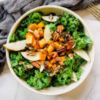 winter salad of warm kale, fresh pear slices, roasted butternut squash and sweet potato chunks, and pecans in a large bowl
