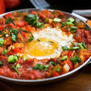 beautiful dish of shakshuka, poached eggs in tomato sauce sprinkled with fresh herbs and spices