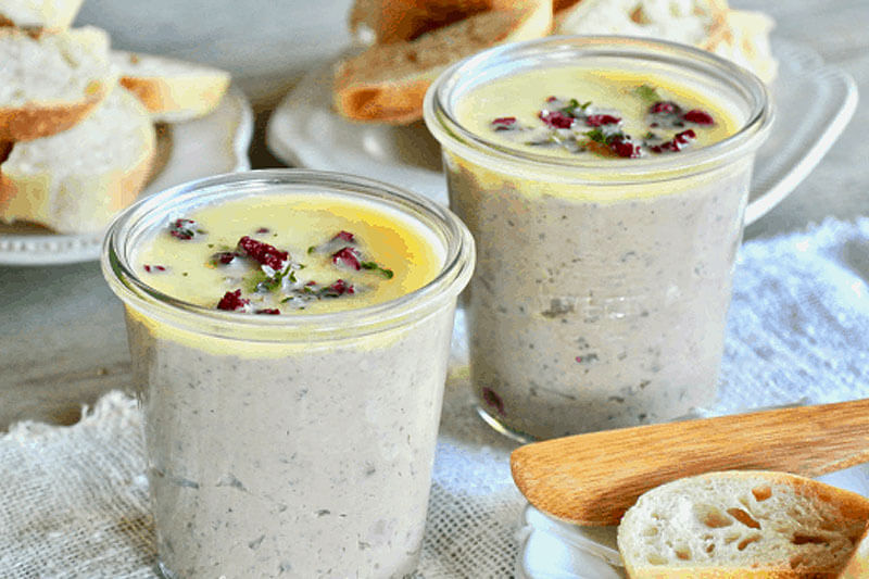 two small glass jars of apple cranberry duck liver pate, with slices of bread in the background