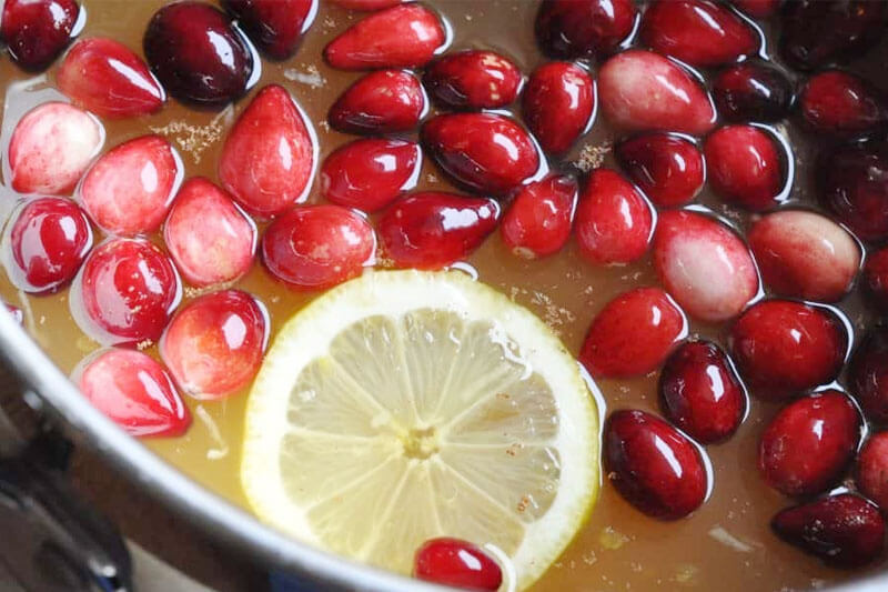 large pot of cranberry wassail, with cranberries floating in the golden colored liquid next to a lemon slice