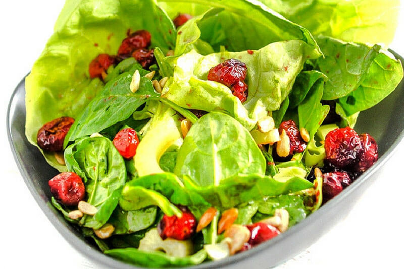 fresh green salad with spinach, avocado, nuts, and cranberries