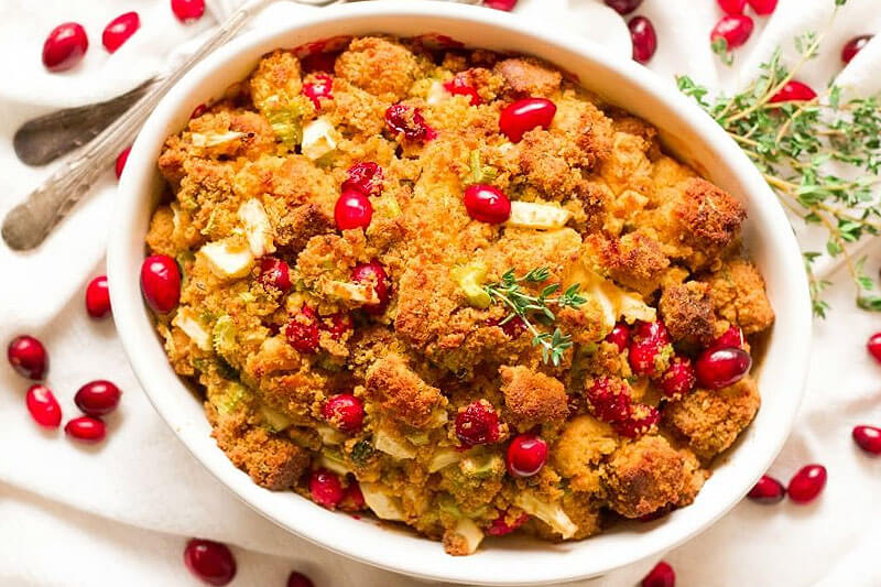 cranberry cornbread stuffing in a white ceramic casserole dish on a white cloth, with fresh thyme and cranberries sprinkled artfully around