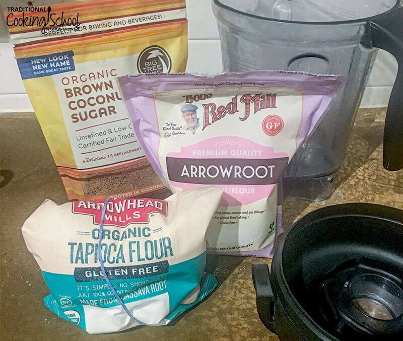 array of ingredients, including organic brown coconut sugar, arrowroot powder, and organic tapioca flour, on a countertop next to a Vitamix blending container and lid