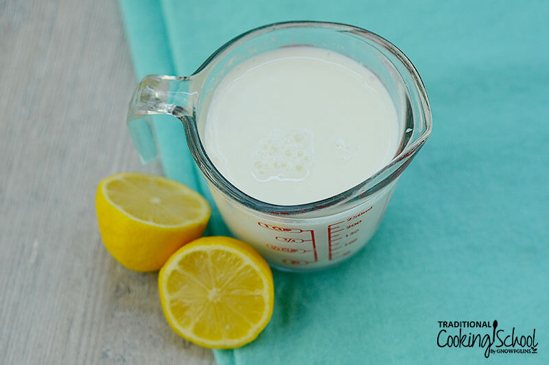 Pyrex measuring cup full of milk, next to two lemon halves on a blue cloth