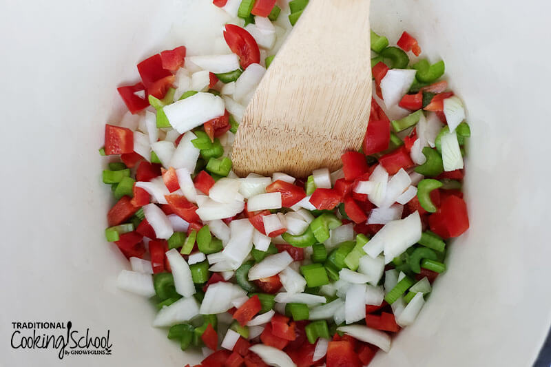 overhead shot of sauteing veggies (onions, celery, and peppers) in a pot with a wooden spoon