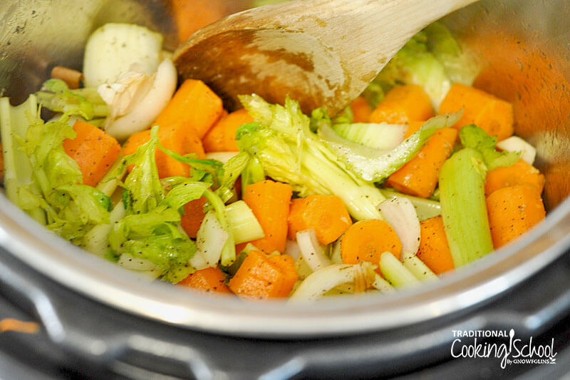 close-up shot of sauteing vegetables in the Instant Pot with a wooen spoon