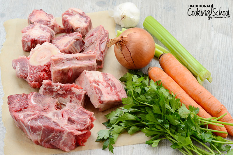 array of ingredients for making broth, including beef bones, fresh cilantro, celery, carrots, onion, and garlic