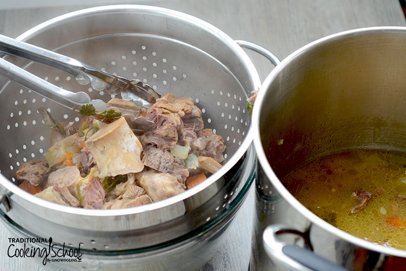 straining veggies and bones out of beef broth with a stainless steel colander
