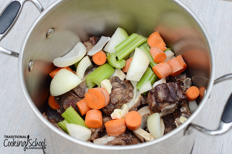 stainless steel pot of bones and veggies for making bone broth