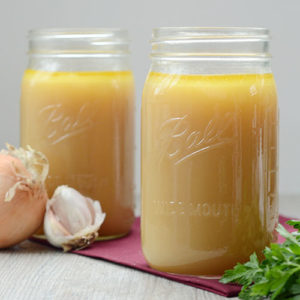 two quart-sized glass jars of beef bone broth next to fresh herbs, onion, and garlic
