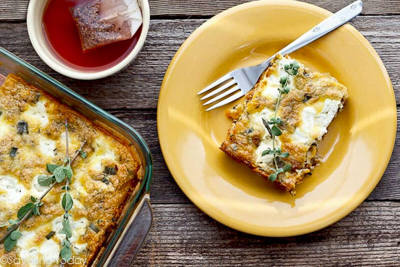 slice of butternut squash quiche with Italian sausage and sage on a yellow ceramic plate next to a fork, with the casserole dish beside it and a cup of tea