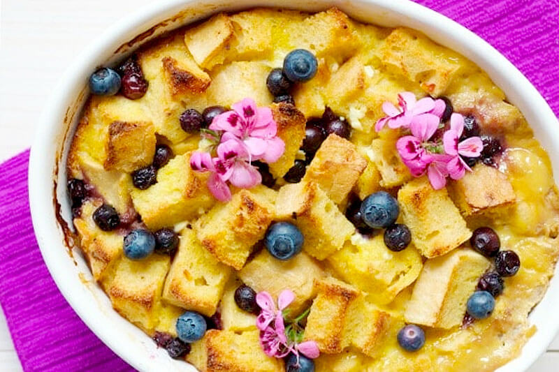 lemon blueberry breakfast strata garnished with fresh blueberries and pink flowers
