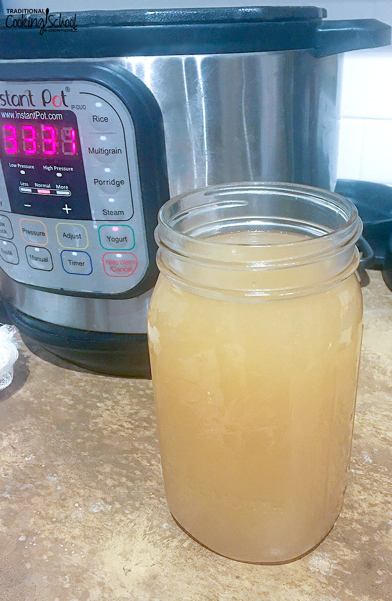 quart-sized glass Mason jar of raw apple cider vinegar on a counter with an Instant Pot in the background
